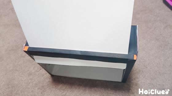 箱の上部に切り込み線を入れテレビ画面に見立てた厚紙を差し入れる様子