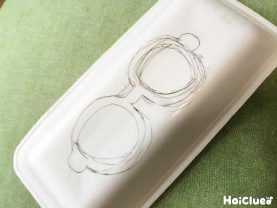 食品トレーの底にメガネの絵を描いた写真