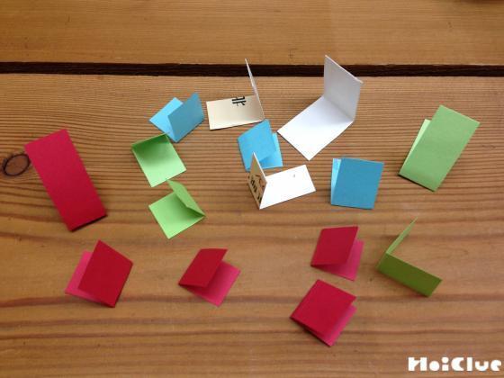 たたんだ折り紙を半分に折ったものをたくさん準備した写真
