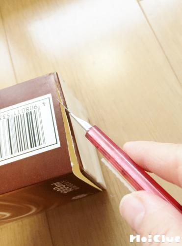 牛乳パックの底をカッターで切っている写真