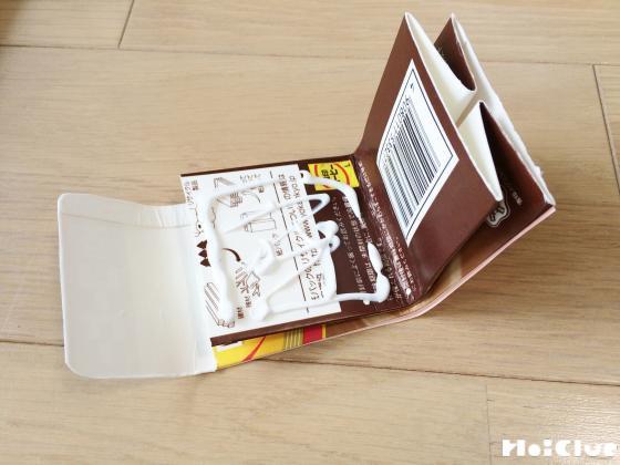 牛乳パックを折り曲げて貼り付けている写真