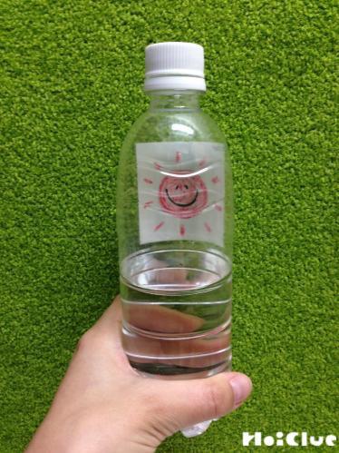 ペットボトルに水をいれて絵を描いた画用紙を外側に貼った写真