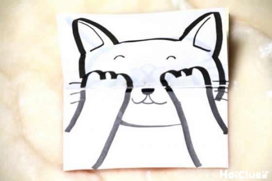 貼り合わせた折り紙の白い面に猫の顔を手で隠した絵を描いた写真