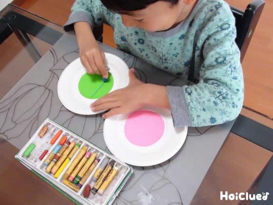 紙皿にそれぞれ違う色の折り紙を貼った写真