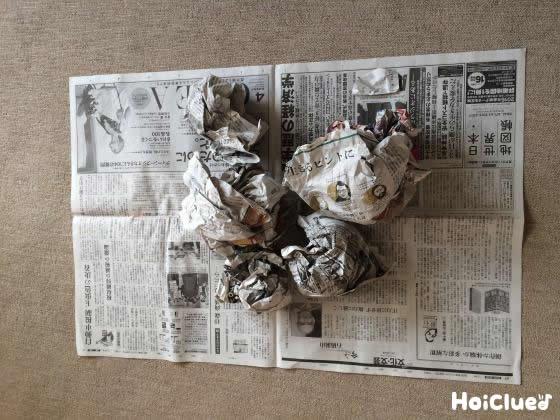 新聞紙の上に丸めた新聞紙を置いた様子