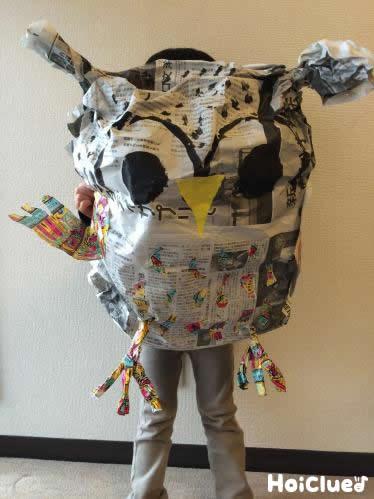 新聞紙で作った大きなミミズクを持つ子どもの写真