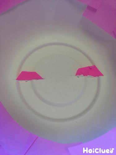 紙皿の底に開けた穴に耳のパーツを差し込む様子