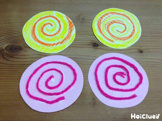 丸い色画用紙に渦巻きを描いたものと、毛糸を渦巻き状に貼った写真