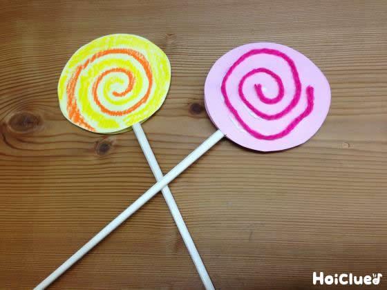 渦巻きを描いた画用紙2枚を割り箸で挟んで張り合せ、完成したペロペロキャンディーの写真