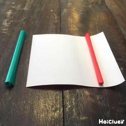 折り紙を細く巻いて中に入れる物を作っている写真