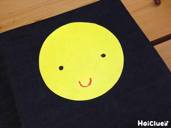 黄色い画用紙を丸く切り取り顔を描いた写真