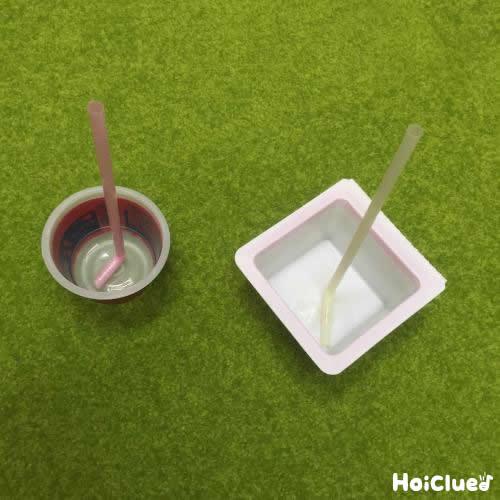 プリンカップと豆腐の容器の中にストローを固定する様子