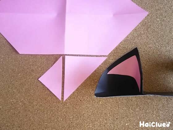 三角形に切った折り紙を耳の内側に貼る様子