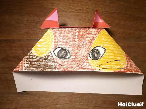 模様を描いたコピー用紙を猫の頭になるよう折り、耳を取り付け完成した写真