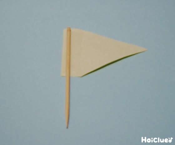 爪楊枝に三角の折り紙をつけて旗にした写真