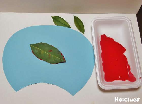 画用紙に絵の具をつけた葉っぱを置いた写真