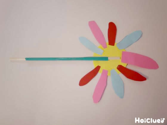 丸い画用紙の周りに花びらの形に切った画用紙を貼り付けた写真