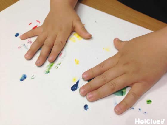 画用紙をぺたぺたと手で色をつけている写真