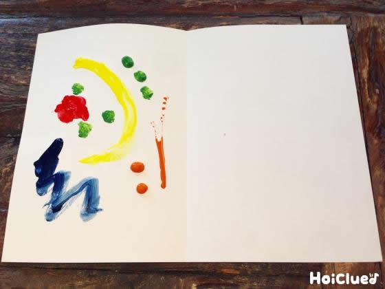 半分に折った画用紙の半分に絵の具をつけた写真