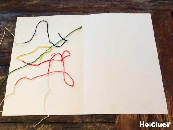 画用紙に糸色をつけた糸を乗せた写真