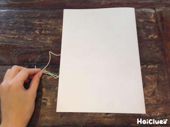 画用紙を半分に折って糸の端を持っている写真