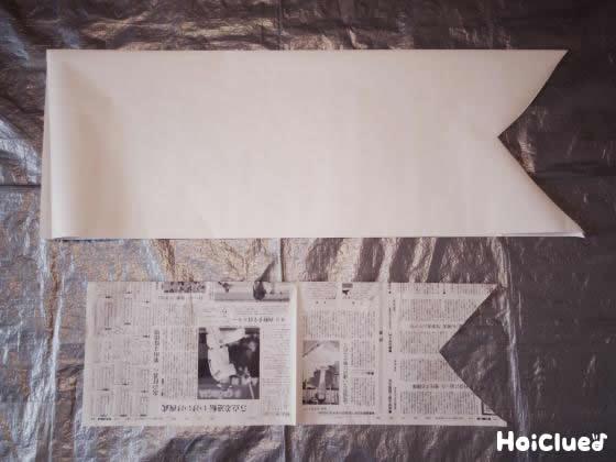 大きな紙と新聞紙をしっぽの形をつけて細長く切り取った写真
