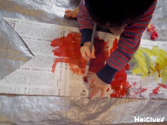 新聞紙に絵の具で色をつけている写真