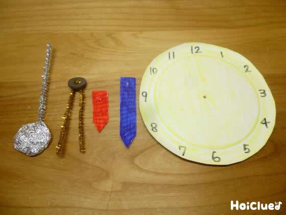 紙皿に時計の文字盤を描き、モールなどで時計用の針を作った写真