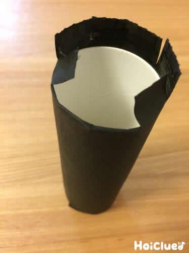 トイレットペーパーの芯に黒い折り紙を巻いている写真