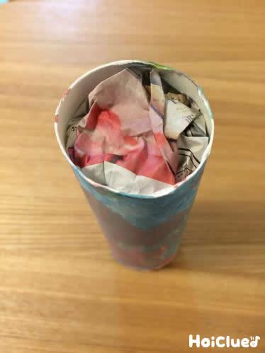 トイレットペーパーの芯の中に新聞紙を入れている写真