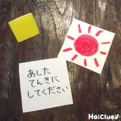 折り紙に願い事を描いている写真