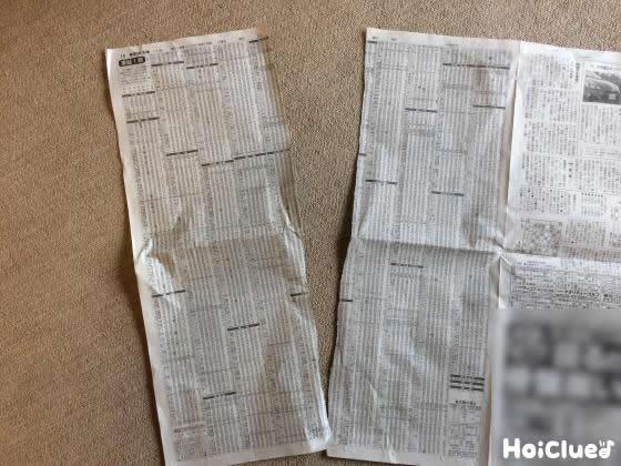広げた新聞紙を4等分にちぎる様子