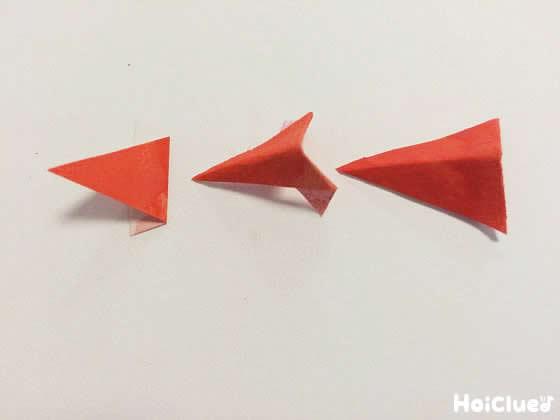 赤い色紙を三角形に切りクチバシの形を作る様子