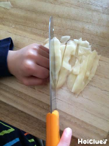 スライスしたジャガイモを細くカットしている写真