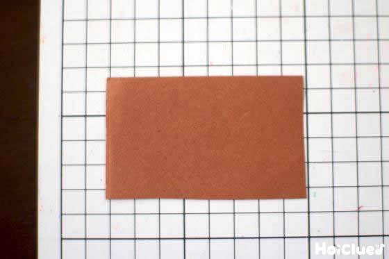 茶色い画用紙を四角く切った写真