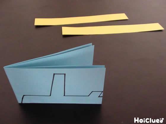 細長く切った2本の画用紙と、4つ折りにし飛行機の絵を描いた画用紙の写真
