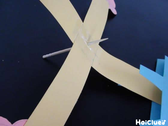 2本の画用紙を十字型に合わせ中心に爪楊枝を刺した様子