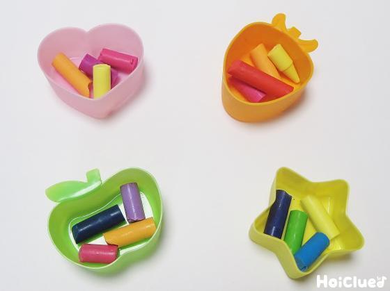 クレヨンを何色か折って容器に入れている写真