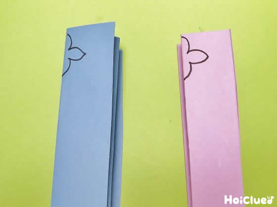 じゃばら折りにした青とピンクの画用紙に半分の花の絵を描いた写真