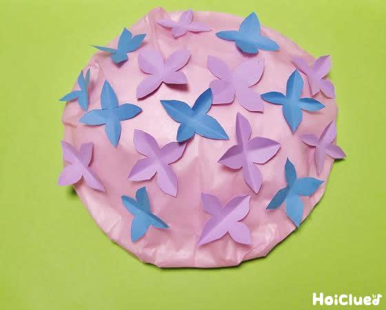 花紙で覆った紙皿に画用紙で作った花を貼り付けた写真