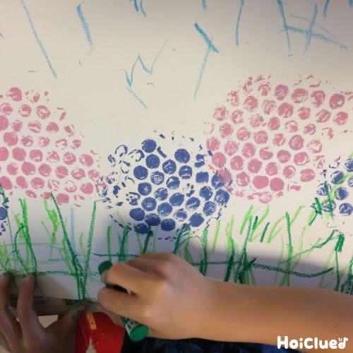 白い紙にスタンプして紫陽花を描いている写真