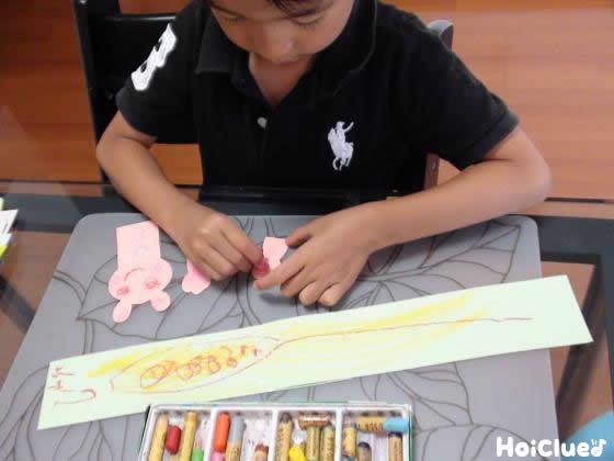 緑の画用紙に絵を描く子どもの様子