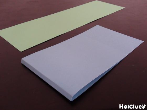 長方形に切った画用紙と、それを中心からずらして2本折り目を付けた写真