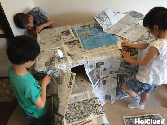 新聞紙をいろいろ貼り付けてる写真