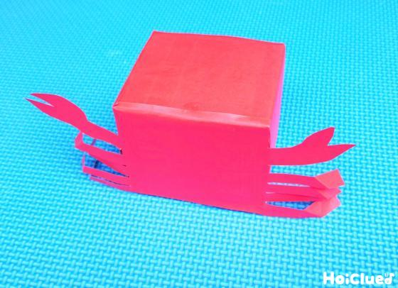 赤い折り紙で覆った空き箱の両サイドにカニの足を貼り付けた様子