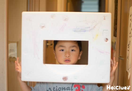 発泡スチロールの穴から顔を出す子どもの写真