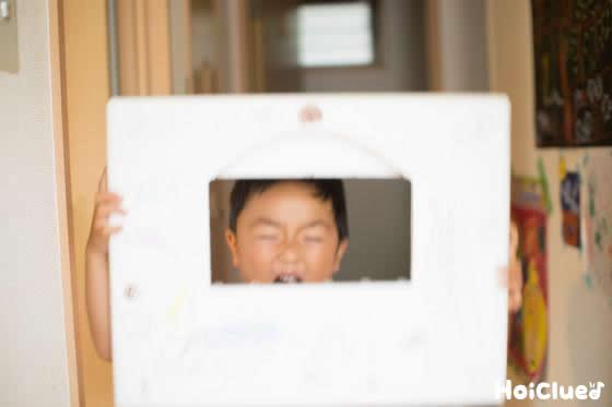 発泡スチロールの穴から顔を出す勇ましい表情の子どもの写真