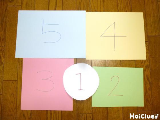 それぞれ少しづづ大きさの違う4枚の四角い色画用紙と、1枚の丸い画用紙