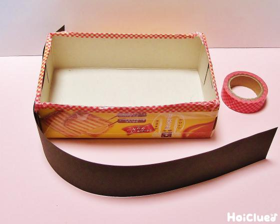 お菓子箱に色画用紙を貼り重箱を作る様子