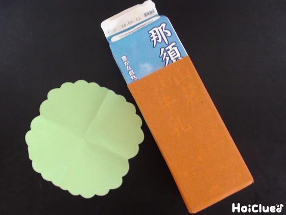 牛乳パックに茶色い折り紙を貼り付けたものと緑色の折り紙で木の葉を作った写真